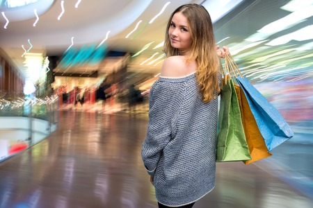 Young happy woman with shopping bags in the mall photo