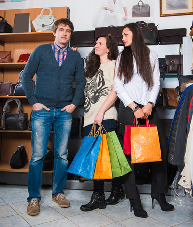 sales assistant: Two young happy woman with shopping bags and male  sales assistant  in the mall Stock Photo