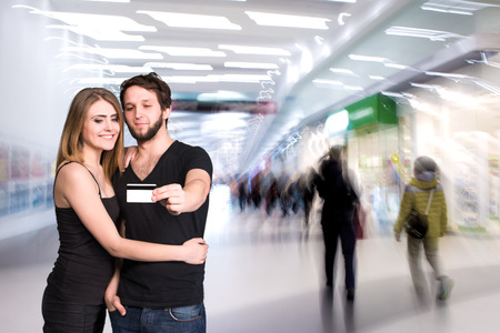 Happy couple with in the mall. Man holding credit card. Focus on credit card photo