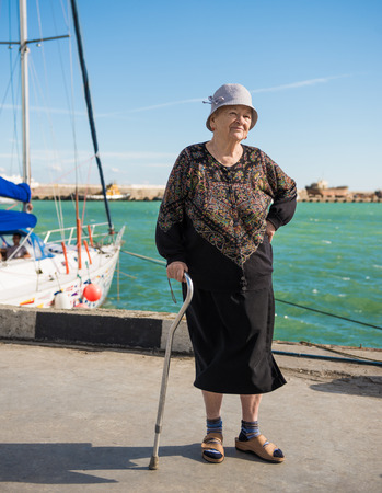 Old woman standing with a cane near yacht harbor
