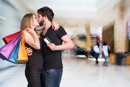 Happy kissing couple with shopping bags at the mall. Man holding credit card photo