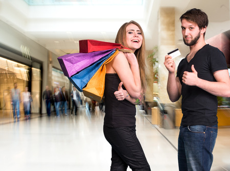 Happy couple with shopping bags at the mall. Man holding credit card photo