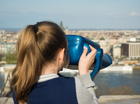 Girl looking at coin operated binocular in Budapest, Hungary