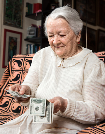 cash money: Old woman holding dollar cash money at home Stock Photo