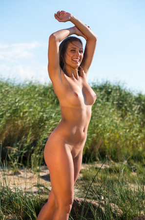 nude pose: Young beautiful nude woman posing on nature background Stock Photo