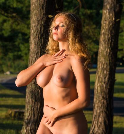 female nudity: Beautiful young nude woman posing outdoor. Enjoying summer time