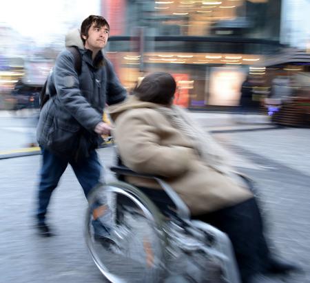 paraplegic: Hombre empujando a la mujer en una silla de ruedas en el desenfoque de movimiento