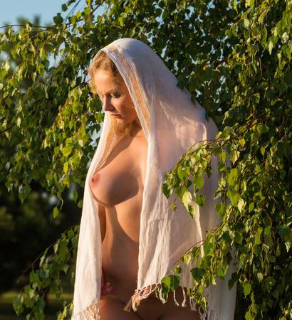 desnudo de mujer: Hermosa joven mujer desnuda posando al aire libre. Disfrutando de la hora de verano Foto de archivo