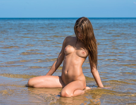 beach breast: Beautiful young naked woman posing on the beach. Enjoying summer time