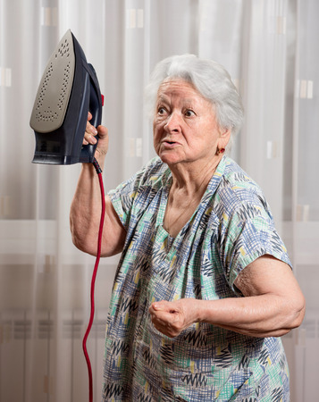 Angry old woman with an iron at home 免版税图像 - 41386852