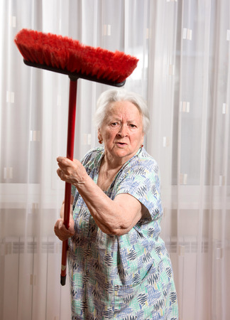 Old angry woman threatening with a broom at home 免版税图像 - 41386907