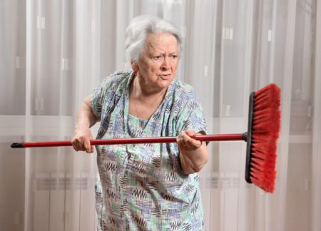 Old angry woman threatening with a broom at home 免版税图像 - 41386911