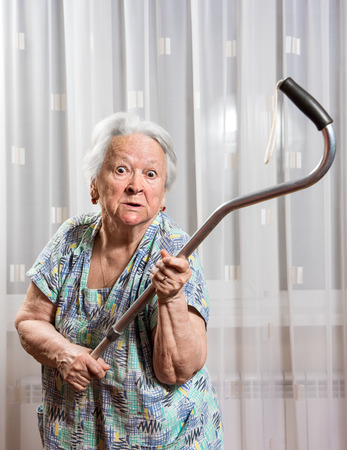threatening: Old angry woman threatening with a cane at home