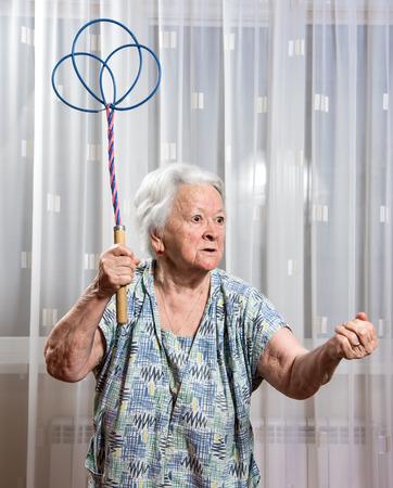 batidora: Vieja mujer enojada amenaza con un sacudidor de alfombras en casa Foto de archivo