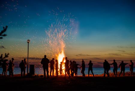Gente que se reclina cerca de grande al aire libre de la hoguera en la noche