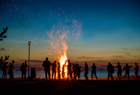 People resting near big bonfire outdoor at night Archivio Fotografico
