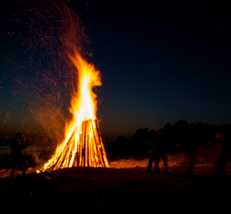 People resting near big bonfire outdoor at night 免版税图像
