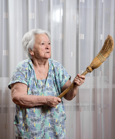 threatening: Old angry woman threatening with a broom at home