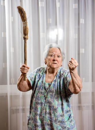 Old angry woman threatening with a broom at home