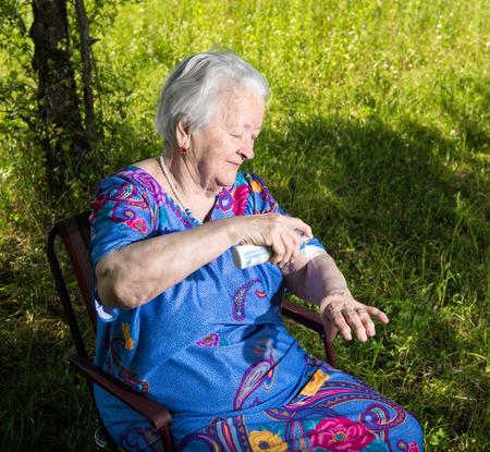 Oude vrouw spuiten insectenwerend middel op de huid outdoor Stockfoto