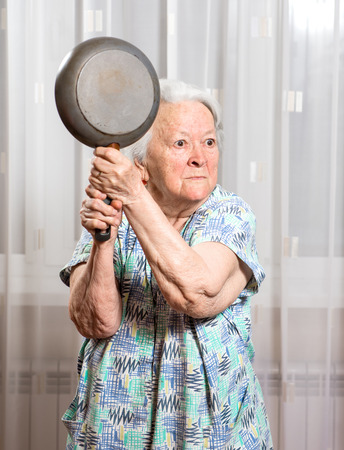 life threatening: Angry old woman with a pan at home