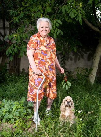 oldage: Beautiful old woman standing in the garden Stock Photo