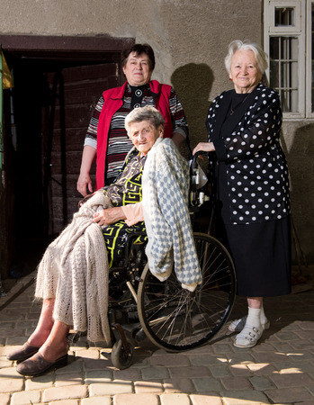 wheel chair: Old woman in wheel chair with daughter and sister outdoors Stock Photo