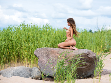 nude nature: Beautiful young naked woman posing on the beach. Enjoying summer time against nature background Stock Photo