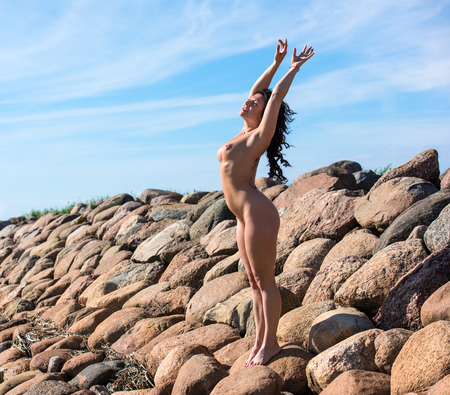 Young beautiful nude woman posing on a stone pier Stock Photo