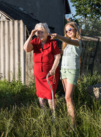 grandkids: Grandmother with a cane and granddaughter outdoor