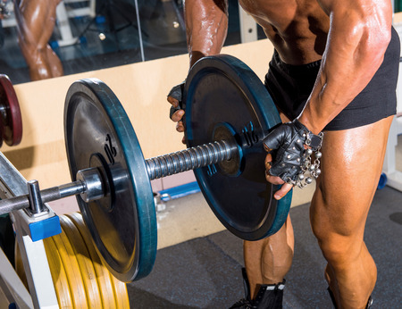 musculation: Muscular handsome bodybuilder working out in gym with barbell Stock Photo