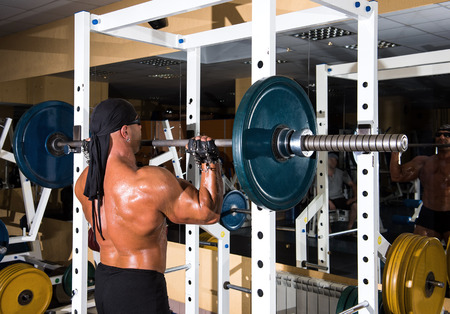 Muscular handsome bodybuilder working out in gym with barbell Stock Photo