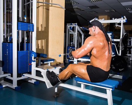 Athlete handsome bodybuilder training  on simulator in the gym