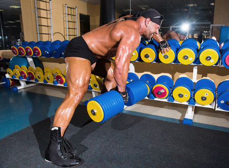 Handsome athletic man bodybuilder doing exercises with dumbbell in gym