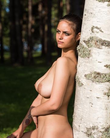 nue plage: Belle jeune femme nue en appréciant l'heure d'été contre la nature de fond Banque d'images