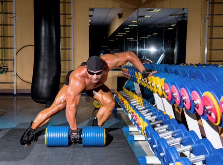 musculation: Handsome athletic man bodybuilder doing exercises with dumbbell in gym