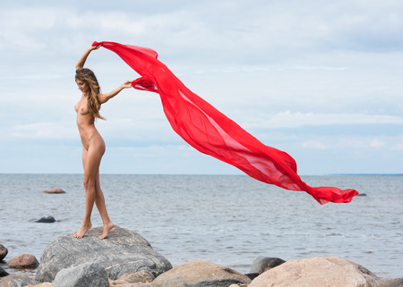 Young naked woman posing on a beach with red fabric 免版税图像 - 44306640
