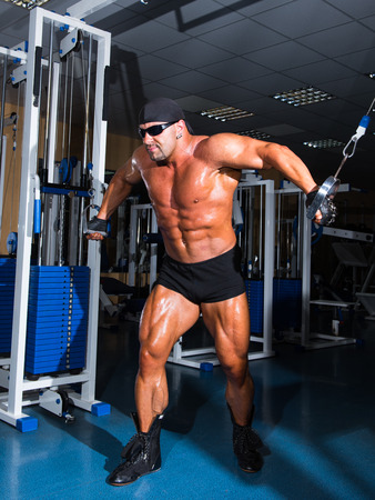 musculation: Athlete handsome bodybuilder training on simulator in the gym
