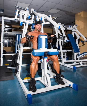 musculation: Athlete handsome bodybuilder training on simulator in the gym