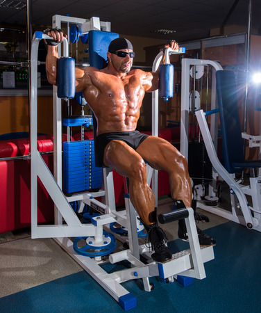 only the biceps: Athlete handsome bodybuilder training on simulator in the gym