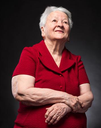 personas mirando: Anciana sonriente que mira para arriba en un fondo oscuro