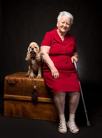 Oude vrouw met Amerikaanse spaniel op een donkere achtergrond