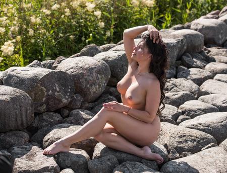 femmes nues sexy: Belle jeune femme nue posant sur un quai de pierre