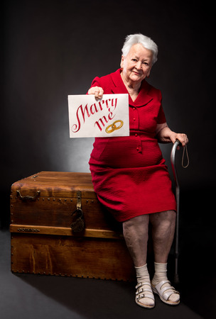 me: Old woman holding Marry Me board on a dark background