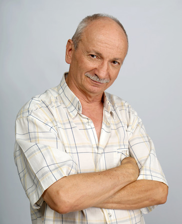 amiable: Portrait of smiling senior man on a gray background Stock Photo