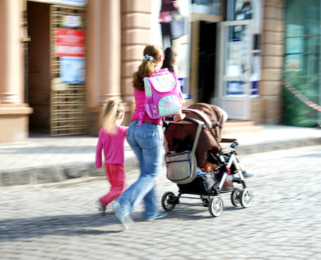 small child: Mother with small child and a stroller walking down the street. Intentional motion blur