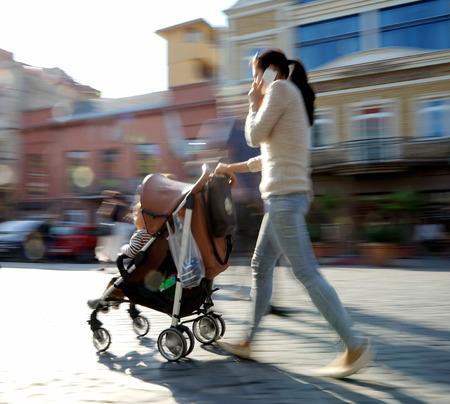 Mutter mit Kleinkind und einem Kinderwagen auf der Straße. Vorsätzliche Bewegungsunschärfe Standard-Bild - 45359802