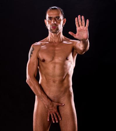 modelos desnudas: Hombre desnudo muscular atractivo que presenta sobre fondo oscuro