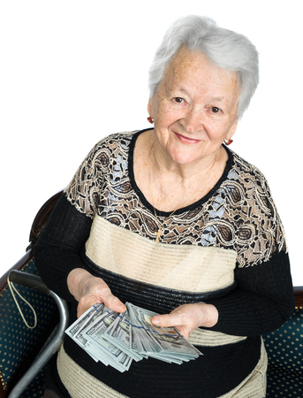 woman holding money: Portrait of old woman holding money in hands on a white background