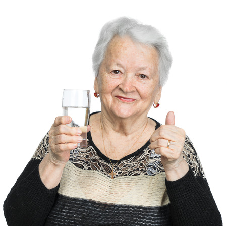 Old woman with glass of water over white background 免版税图像